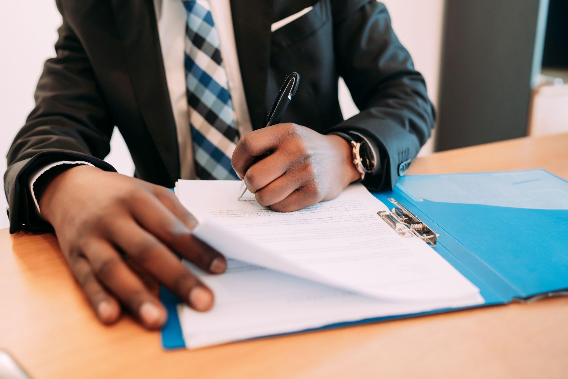 Imagem mostra empreendedor assinando documentação para abrir uma empresa